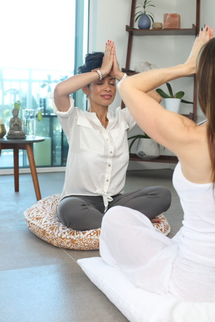 Woman seated on cushion doing yoga